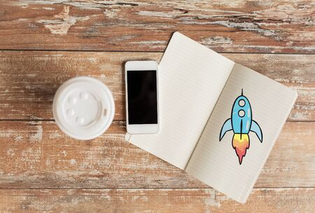 objects paper: business, education, objects and technology concept - close up of coffee paper cup, smartphone and rocket drawing in notebook on table Stock Photo