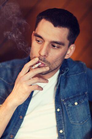 ciggy: people and bad habits concept - young man smoking cigarette at bar Stock Photo