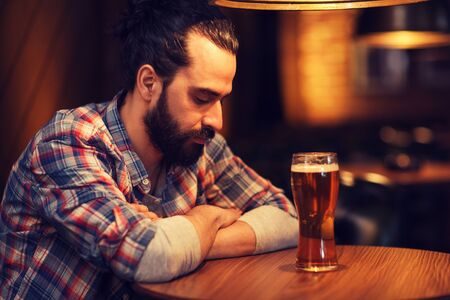 unhappy man: people, loneliness, alcohol and lifestyle concept - unhappy single man with beard drinking beer at bar or pub Stock Photo