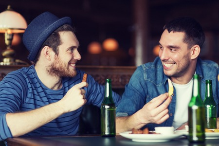 bottled beer: people, leisure, friendship and bachelor party concept - happy male friends drinking bottled beer and talking at bar or pub