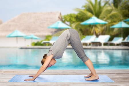 dog pose: fitness, sport, people and healthy lifestyle concept - woman making yoga in downward facing dog pose on mat over beach and swimming pool background