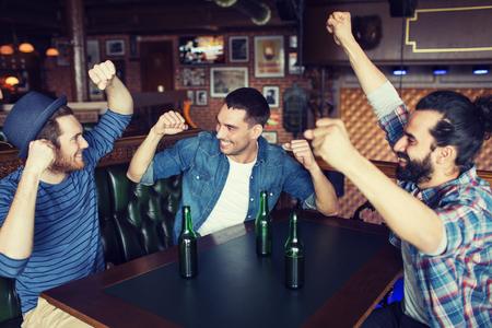 bottled beer: people, leisure, friendship and bachelor party concept - happy male friends drinking bottled beer and raised hands at bar or pub