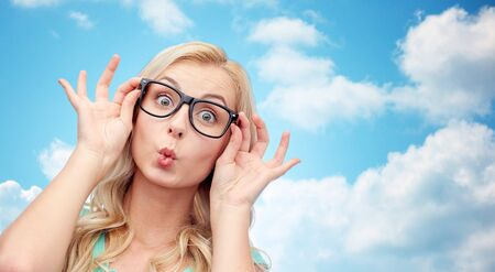 woman  glasses: vision, education and people concept - happy young woman or teenage girl glasses making funny fish face over blue sky and clouds background
