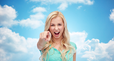 insulting: gesture, emotions, expressions and people concept - happy smiling young woman or teenage girl pointing finger to you over blue sky and clouds background