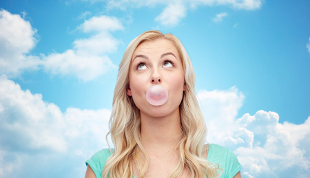 goma de mascar: emotions, expressions and people concept - happy young woman or teenage girl chewing gum over blue sky and clouds background Foto de archivo