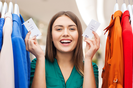 clothing, fashion, sale and people concept - happy woman showing price tags on clothes at shopping center or mall