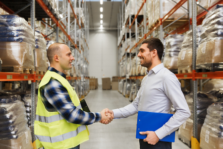 도매, 물류, 사람과 수출 개념 - 클립 보드가 손을 흔들면서 창고에 거래를 가진 육체 노동자와 기업인