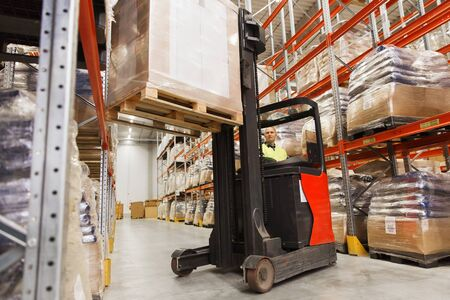 elevator operator: wholesale, logistic, loading, shipment and people concept - man or loader on forklift loading cargo at warehouse