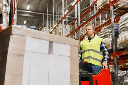 wholesale, logistic, loading, shipment and people concept - man on forklift loader loading boxes at warehouse Stock Photo