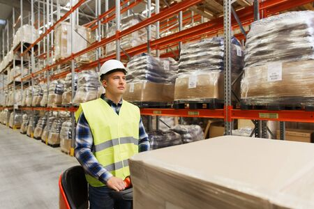 wholesale: wholesale, logistic, loading, shipment and people concept - man or loader on forklift loading cargo at warehouse