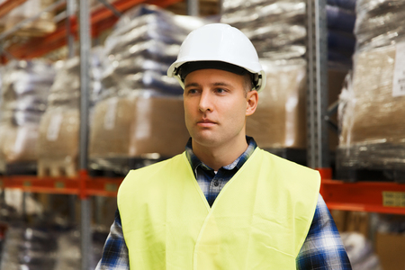garment: wholesale, logistic, people and export concept - man in reflective safety vest and hardhat at warehouse