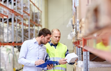 merchandise: wholesale, logistic, people and export concept - manual worker and businessmen with clipboard and box at warehouse Stock Photo