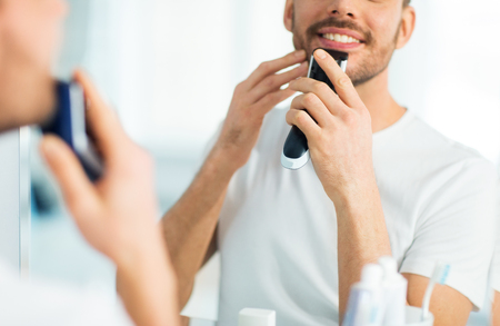 shaver: beauty, shaving, grooming and people concept - close up of young man looking to mirror and shaving beard with trimmer or electric shaver at home bathroom Stock Photo