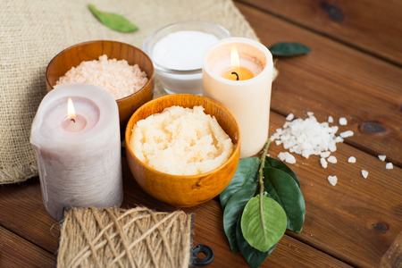 natural therapy: beauty, spa, therapy, natural cosmetics and wellness concept - close up of body scrub with himalayan pink salt and candles on wood