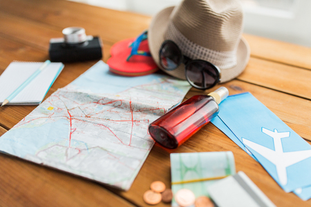 Zomervakantie, toerisme en objecten concept - close-up van reiskaart, vliegtickets, geld en persoonlijke accessoires