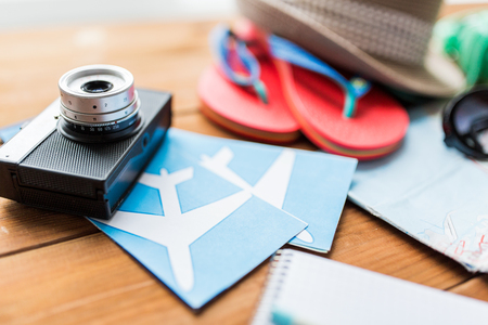 objects: summer vacation, travel, tourism  and objects concept - close up of camera, airplane tickets and personal accessories