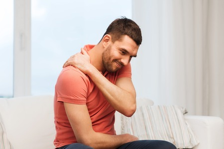 unhappy people: people, healthcare and problem concept - unhappy man suffering from neck pain at home