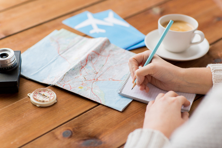 destinations: vacation, tourism, travel, destination and people concept - close up of traveler hands with blank notepad and pencil
