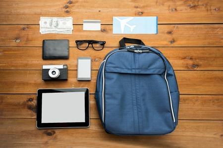 MOCHILA: los viajes, el turismo, la tecnología y los objetos concepto - cerca de smartphone con el ordenador de la PC de la tableta, billete de avión y cosas personales