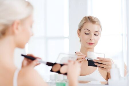highlights: beauty, make up, cosmetics, morning and people concept - young woman with makeup brush and contouring and highlighting palette looking to mirror at home bathroom