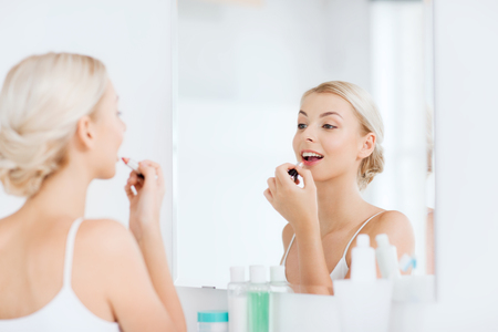 applying: beauty, make up, cosmetics, morning and people concept - smiling young woman with lipstick applying makeup and looking to mirror at home bathroom