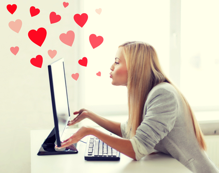 computer office: virtual relationships, online dating and social networking concept - woman sending kisses with computer monitor