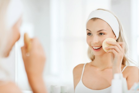 beauty, skin care and people concept - smiling young woman washing her face with facial cleansing sponge at bathroom