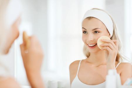 아름다움, 피부 관리 및 사람들 개념 - 욕실에서 얼굴 클렌징 스폰지로 그녀의 얼굴을 세척 웃는 젊은 여자