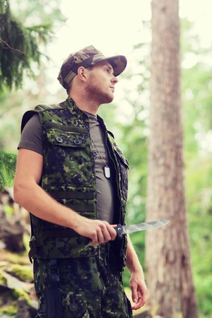 ranger: hunting, war, army and people concept - young soldier, ranger or hunter with knife in forest Stock Photo