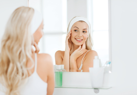 schoonheid, huidverzorging en mensen concept - lachende jonge vrouw in haarband raken haar gezicht en op zoek naar spiegel thuis badkamer