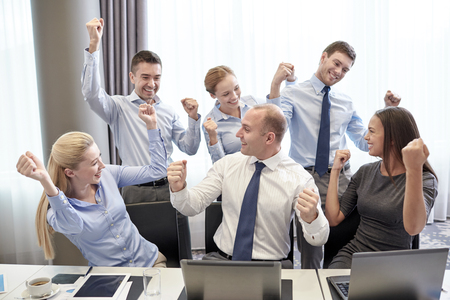 business, people, technology, gesture and teamwork concept - smiling business team raising hands and celebrating victory in office Stock Photo