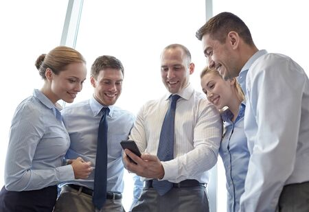 international business: business, teamwork, people and technology concept - business team looking to smartphone in office Stock Photo
