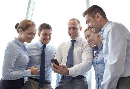 negocios internacionales: negocio, trabajo en equipo, personas y tecnología concepto - equipo de negocios que buscan smartphone en oficina Foto de archivo