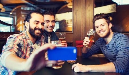 la gente, el ocio, la amistad, la tecnología y el concepto de la despedida de soltero - amigos hombres felices con el teléfono inteligente teniendo autofoto y bebiendo cerveza en el bar o pub