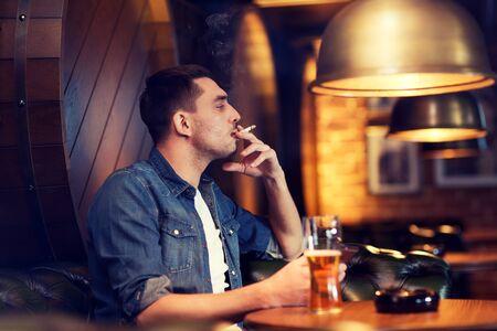 malos habitos: las personas y los malos hábitos concepto - hombre de beber cerveza y fumar cigarrillos en el bar o pub Foto de archivo