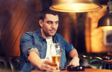 malos habitos: people and bad habits concept - young man drinking beer and smoking cigarette at bar or pub Foto de archivo
