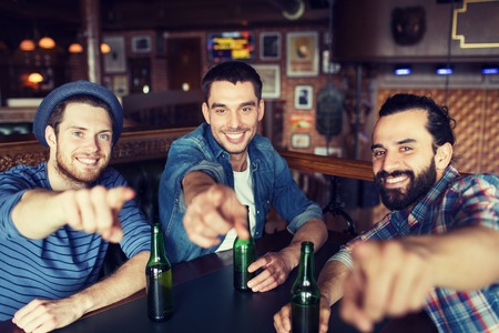 bottled beer: people, leisure, friendship and bachelor party concept - happy male friends drinking bottled beer and  and pointing on you at bar or pub Stock Photo