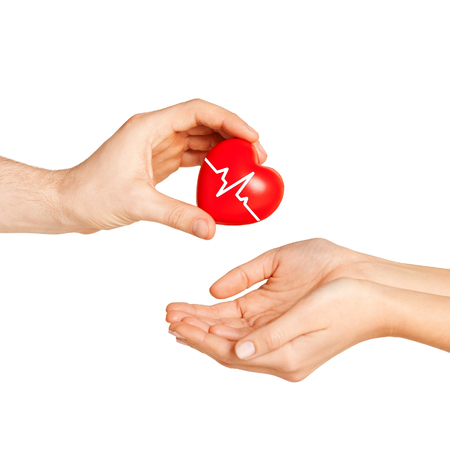 health woman: charity, health care, donation and medicine concept - man hand giving red heart with cardiogram to woman Stock Photo