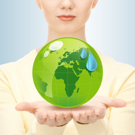 earth day, people, ecology and environment concept - close up of woman holding green globe in her hands photo