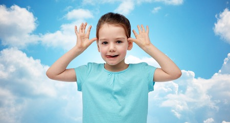 clouds making: childhood, fashion, fun and people concept - happy little girl having fun and making ears over blue sky and clouds background Stock Photo