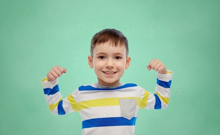 arms up: childhood, power, education, gesture and people concept - happy smiling little boy with raised hand over green school chalk board background