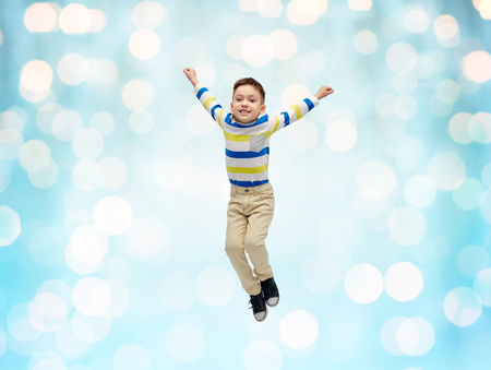 fly: happiness, childhood, freedom, movement and people concept - happy little boy jumping in air over blue holidays lights background Stock Photo
