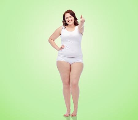 natural backgrounds: gesture, weight loss and people concept - smiling young plus size woman in underwear showing thumbs up over green natural background