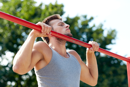 grapple: fitness, sport, exercising, training and lifestyle concept - young man doing pull ups on horizontal bar outdoors