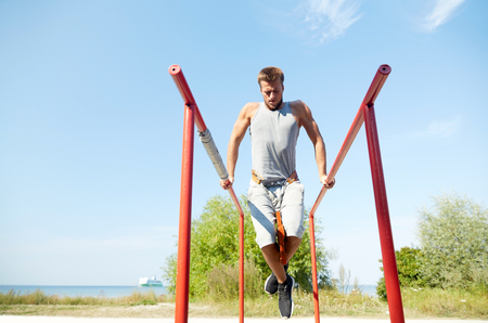 calisthenics: fitness, sport, exercising, training and lifestyle concept - young man doing triceps dip with weight belt on parallel bars outdoors Stock Photo