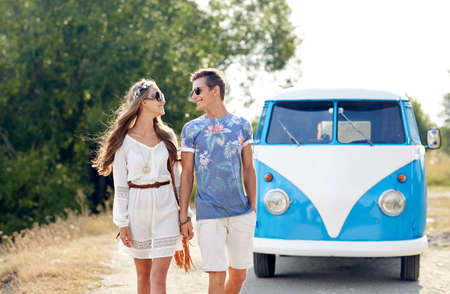 minivan: summer holidays, road trip, vacation, travel and people concept - smiling young hippie couple talking over minivan car