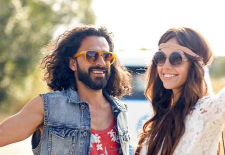 trip over: summer holidays, road trip, vacation, travel and people concept - smiling young hippie couple over minivan car