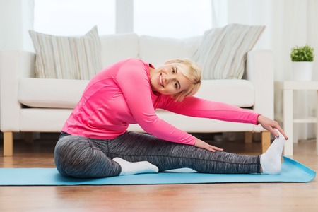 position: fitness, sport, people and healthy lifestyle concept - happy plus size woman stretching leg on mat at home