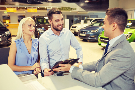 new car: auto business, sale and people concept - happy couple with dealer buying car in auto show or salon