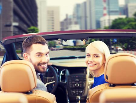 detras de: conducir, transporte de automóviles y el concepto de la gente - cerca de la feliz pareja conducción en el coche descapotable de la parte posterior sobre el fondo calle de la ciudad Foto de archivo